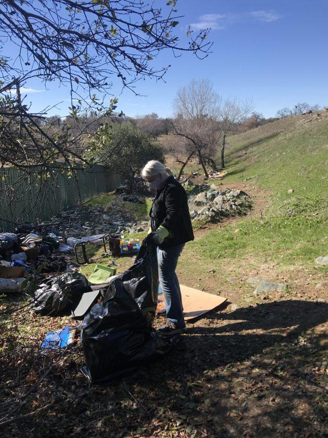 Volunteer, Caryl Callsen, bags trash near Wicklow Way.